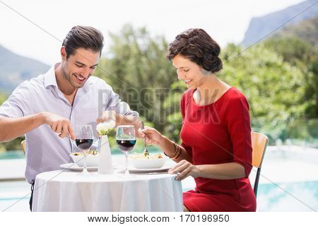 Smiling couple having food while sitting at poolside