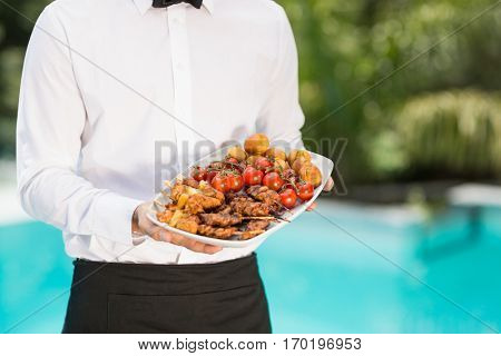 Midsection of waiter holding food tray at poolside