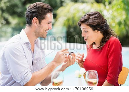 Young man giving engagement ring to surprised woman while sitting at poolside