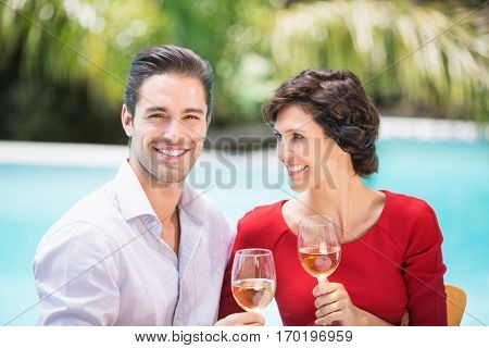 Cheerful couple holding white wine while sitting at poolside