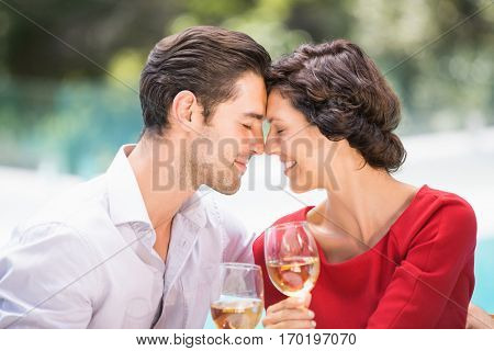 Romantic couple with eyes closed while holding white wine at poolside