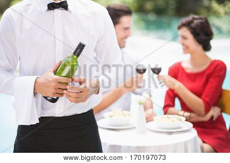 Midsection of waiter holding wine bottle with couple sitting on background