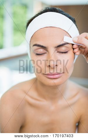 Close-up of woman with eyes closed while receiving face waxing at spa