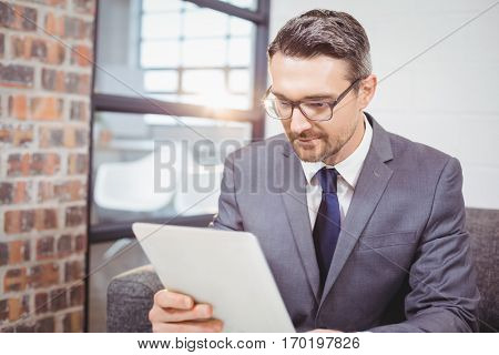 Business proffesional using digital tablet while sitting on sofa in office