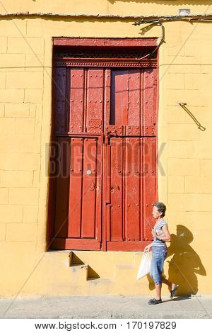 Santiago de Cuba Cuba - 13 january 2016: woman wolking in front of a old wooden door at Santiago de Cuba Cuba