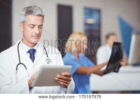 Male doctor using digital tablet with colleague checking X-ray at hospital