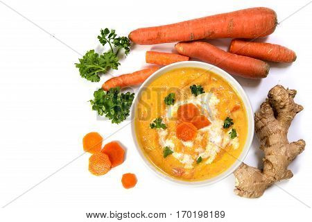 Carrot cream soup with ingedients ginger root raw carots and parsley garnish areal view from above isolated on a white background with copy space