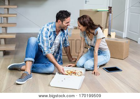 Happy couple having pizza while sitting at home