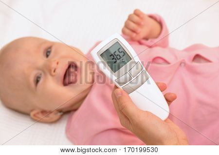 Mother measuring babys temperature with contactless thermometer