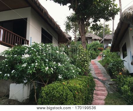 Amazing landscape with bungalow and stone steps. Tropical vacation. Resort with white houses.