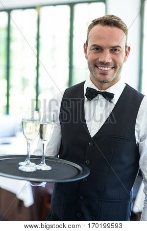 Waiter holding tray of champagne in a commercial kitchen