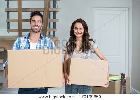 Cheerful couple with boxes at home
