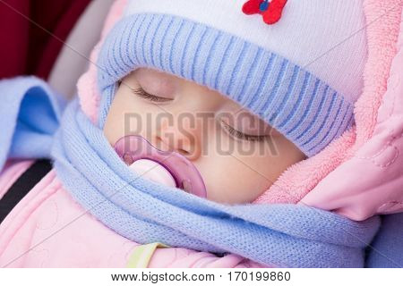 Muffled baby sleeping with dummy in mouth