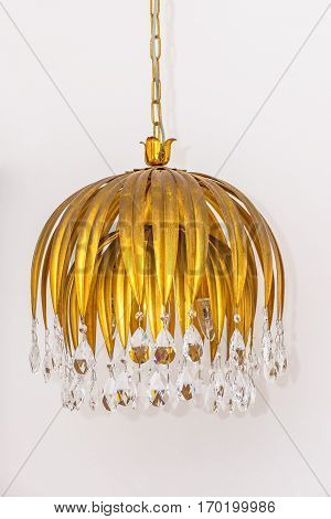 Small chandelier with crystal decorations hanging on white background