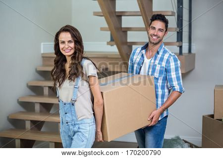 Portrait of cheerful couple with cardboard boxes at home