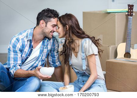 Romantic couple having noodles while sitting in new house