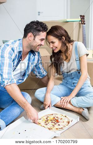 Smiling couple having pizza while sitting in new house