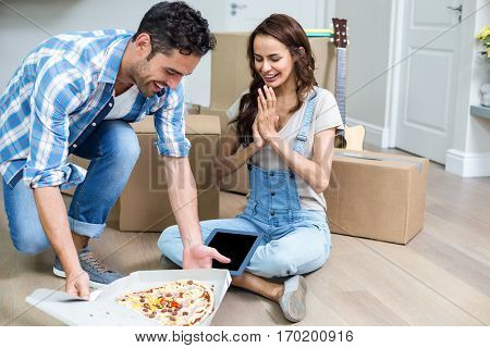 Cheerful couple having pizza while sitting in new house
