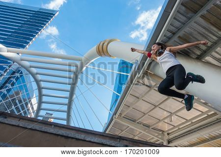 Asian woman jumping high into the sky in the city.