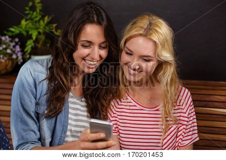 Smiling friends watching a smartphone together at the coffee shop