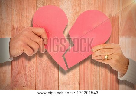 Couple holding a broken paper heart against overhead shot of desk