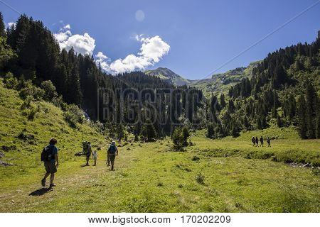 Peoplae hiking in bucolic green summer alpine landscape Swiss Alps mountain massif canton du Valais Switzerland