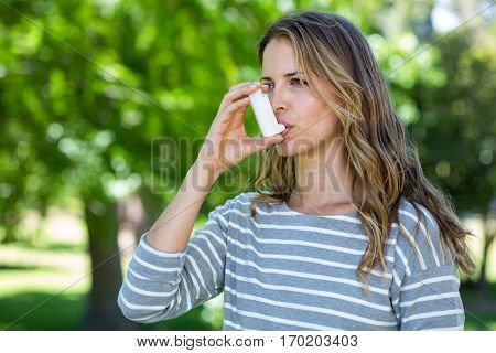 Woman using asthma inhaler in a park