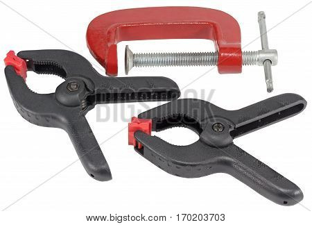 red G-clamps and a spring loaded plastic A-clamp on white background