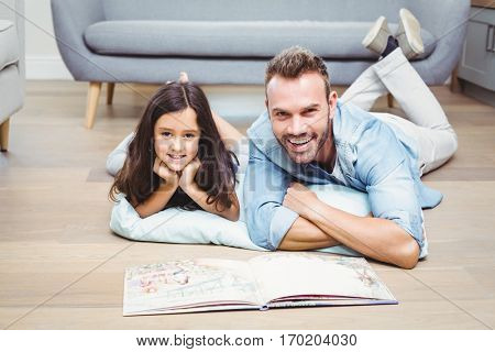 Portrait of father and daughter with picture book lying on floor at home