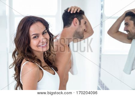 Close-up portrait of woman smiling while man looking in mirror at bakground