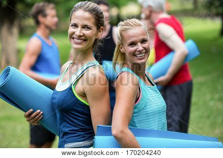 Fit women posing with sports mats back to back in the park