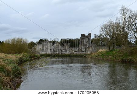 Irish castle ruins with a river running in the foreground.