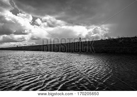 Dramatic Dutch landscape with canal dike and threatening clouds before a storm