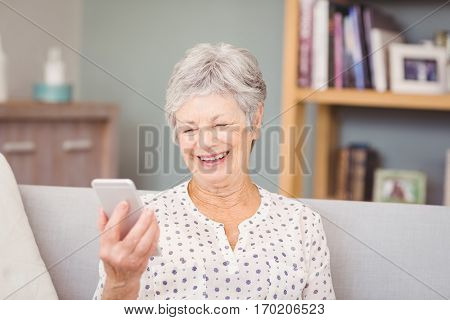 Senior woman holding mobile phone at home