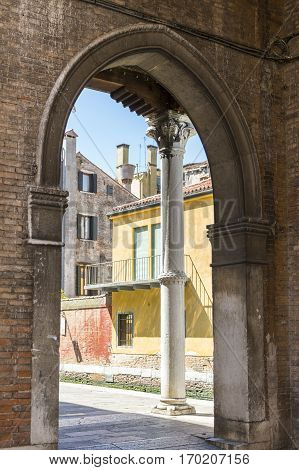 Venitian architecture with old yellow buildings background viewed from an arched passageway