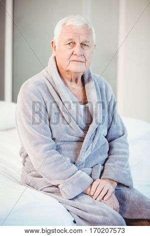 Portrait of suffering senior man sitting on bed at home