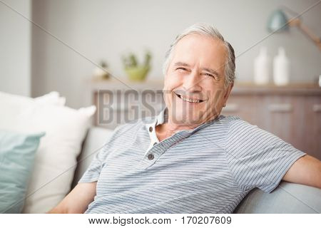 Portrait of happy senior man smiling at home