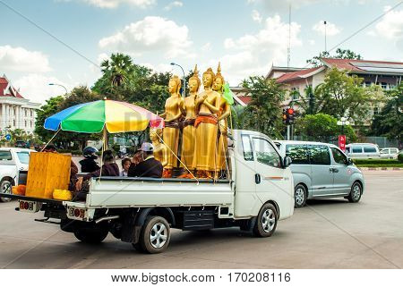 Vientiane, Laos - November 20, 2015: Buddha statues on the back of a car in traffic together with other passenger sitting under a parasol