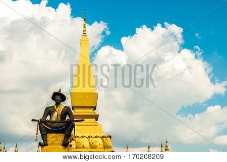 The Great Stupa with statue of King sitting in front of it in Vientiane, Laos