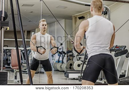 Handsome blond young man exercising pecs on gym equipment, shot from a side