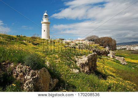 White old lighthouse over meadow covered by grass yellow flowers and rocks against the background of scenic sky