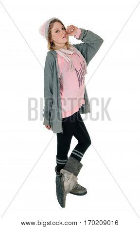 A lovely young woman standing in profile with a knitted hat black tights and boots isolated for white background.