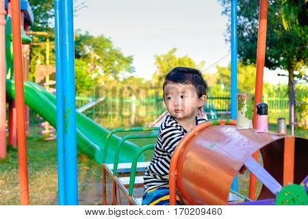 Young Asian Boy Play A Iron Train Swinging At The Playground Under The Sunlight In Summer.