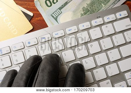 Hacking concept. Hand in black glove is typing on a keyboard.