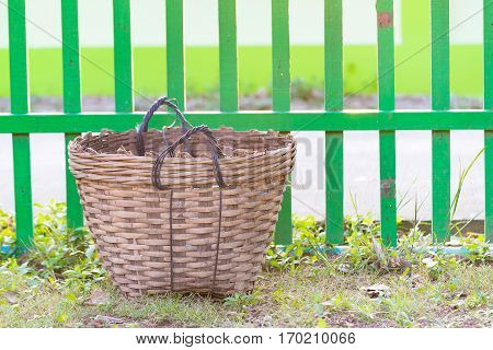 Weave trash basket Dustbin made from bamboo weaving on grass field. fence background.