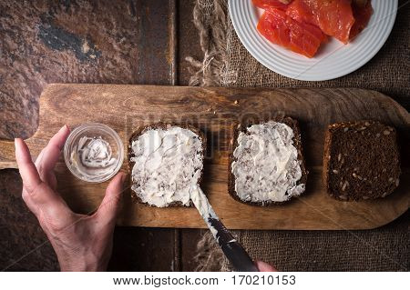 Smearing butter on bread slices of salmon horizontal