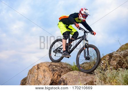 Professional Cyclist Riding the Bike on the Top of the Rock. Extreme Sport Concept. Free Space for Text.