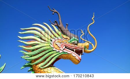 An image of dragon Chinese temple. Dragon statue under blue dragon sky.