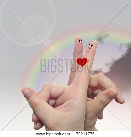 Concept or conceptual human or female hands with two fingers painted with a red heart and smiley faces over rainbow sky background for valentine, romantic, love, couple, young, family or wedding