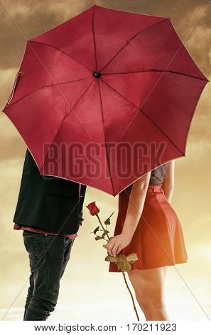Girlfriend and boyfriend having a passionate kiss hidden behind the umbrella
